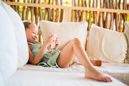 Photo pour Adorable little girl playing on a portable game device or phone - image libre de droit