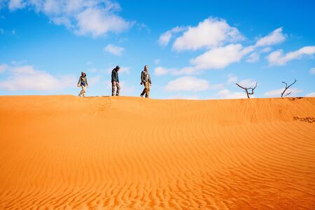 Photo for Family of father and two kids climbing up red sand dune in Namib desert - Royalty Free Image