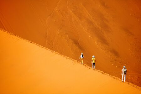 Photo for Family of mother and two kids climbing up famous red sand dune Big Daddy in Sossusvlei Namibia - Royalty Free Image