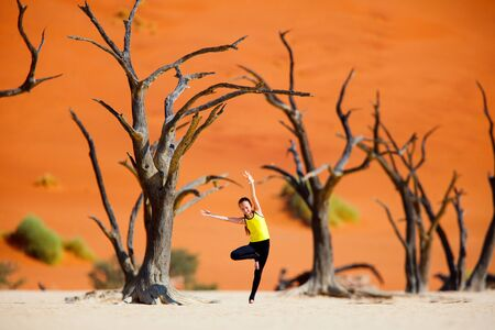 Photo for Adorable young girl among dead camelthorn trees surrounded by red dunes in Deadvlei in Namibia - Royalty Free Image