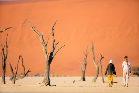Photo for Back view of family mother and daughter walking among dead camelthorn trees surrounded by red dunes in Deadvlei in Namibia - Royalty Free Image