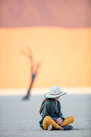 Photo for Young girl against dead camelthorn trees and red dunes in Deadvlei in Namibia - Royalty Free Image