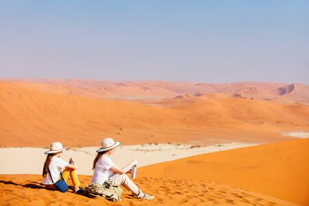 Photo for Family of mother and daughter resting while climbing up famous red sand dune Big Daddy in Sossusvlei Namibia - Royalty Free Image