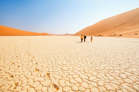 Photo for Back view of family father and two kids walking at white clay pan surrounded by red dunes in Deadvlei in Namibia - Royalty Free Image