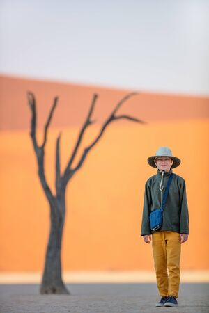 Photo for Adorable girl among dead camelthorn trees surrounded by red dunes in Deadvlei in Namibia - Royalty Free Image