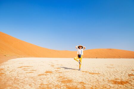 Photo for Adorable young girl surrounded by red dunes in Deadvlei in Namibia - Royalty Free Image