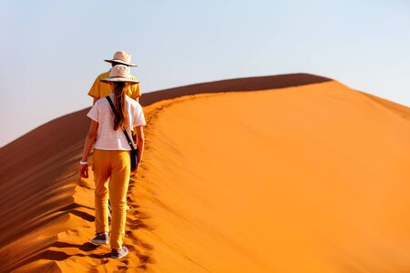 Photo for Kids brother and sister climbing up famous red sand dune Big Daddy  in Sossusvlei Namibia - Royalty Free Image