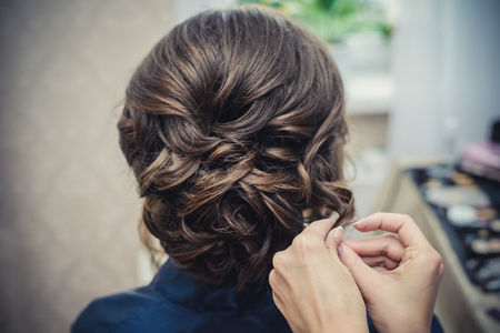 Foto de The hands of the hairdresser do bridal hairstyle with curls for long brown hair closeup - Imagen libre de derechos