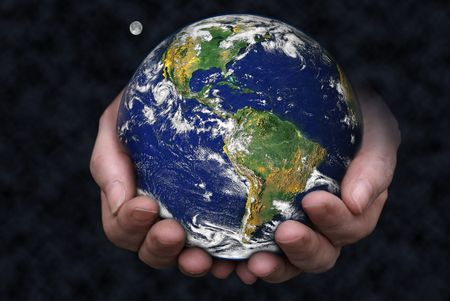 A pair of hands holding the Earth with the moon in the background.