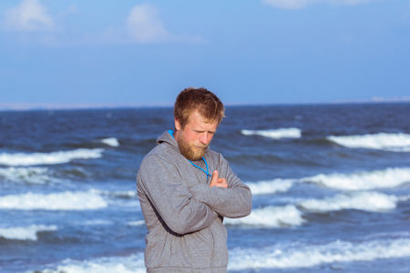 Photo for portrait of young blonde bearded man in gray hoody walking on the beach in dreamy mood - Royalty Free Image