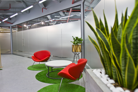 Photo pour A luxurious sitting area in a small office with a modern interior design. Modern Interior of Cafe with Red Chairs and Green Plants - image libre de droit