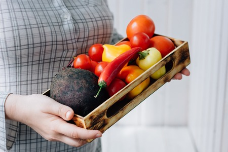 Senior woman holding a box with vegetables in hands