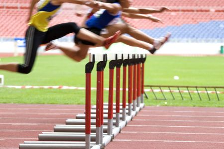 Image of hurdles in action at a stadium with intentional blurring to portray speed.