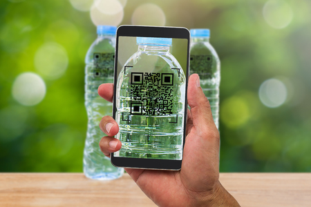 Foto de Man's hands holding smartphone scanning QR code on drinking water bottle in the garden, business concept - Imagen libre de derechos