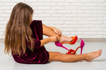 Photo for Little girl sitting on the floor trying on big bright fashionable mother's high-heeled shoes - Royalty Free Image