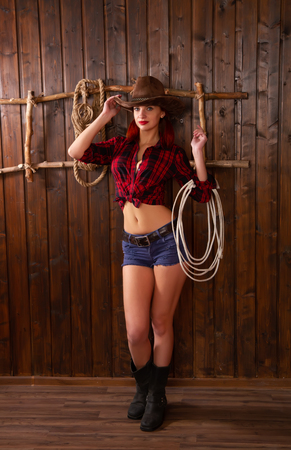 Photo pour long-standing girl dressed as a cowboy wearing a traditional wide-brimmed hat and shertah posing against a wooden background and a ladder - image libre de droit
