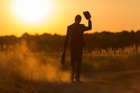 Photo for A lucky young man with bag and hat walks in the sundown - Royalty Free Image