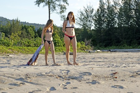 The small fine daughter together with the young mum have a rest on a wild beach against a sea and mountain landscape.