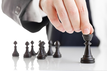 Foto de Business man moving chess figure with team behind - strategy or leadership concept - Imagen libre de derechos