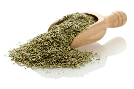 Dried rosemary leaves in wooden scoop over white background