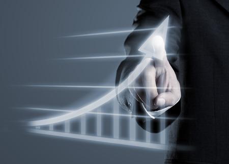 Foto de Businessman drawing success graph on virtual futuristic computer display - Imagen libre de derechos