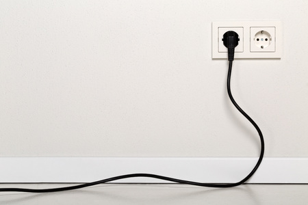 Photo pour Black power cord cable plugged into european wall outlet on white plaster wall with copy space - image libre de droit