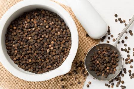 Photo pour Raw, natural, unprocessed black pepper peppercorns in mortar and metal spoon on white wooden table - image libre de droit
