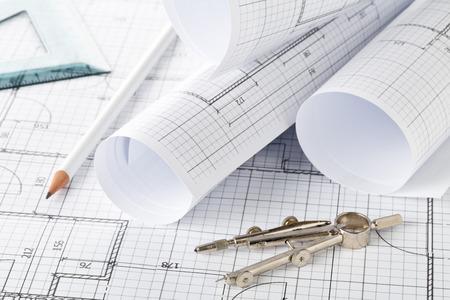 Foto de Rolls of architectural blueprint house building plans on blueprint background on table with pencil, square and compasses - Imagen libre de derechos