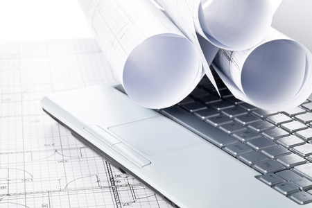 Photo pour Rolls of architectural blueprint house building plans on laptop computer keyboard on blueprint background on table - image libre de droit