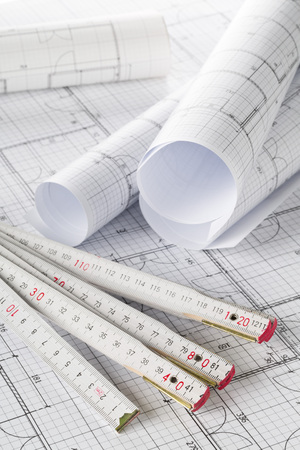 Photo pour Rolls of architectural blueprint house building plans with folding rule on blueprint background on table - image libre de droit