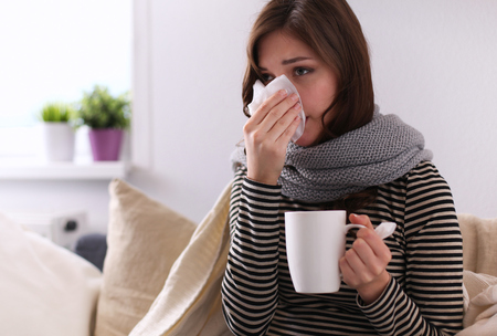 Foto de Sick woman covered with blanket holding cup of tea sitting on sofa couch - Imagen libre de derechos