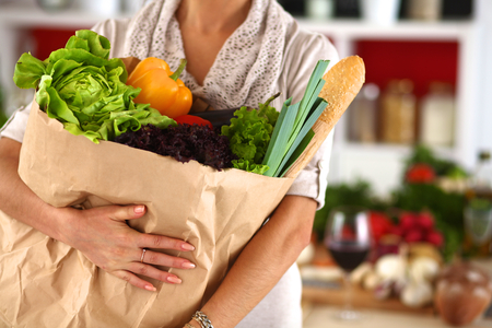 Photo pour Young woman holding grocery shopping bag with vegetables Standing in the kitchen. - image libre de droit