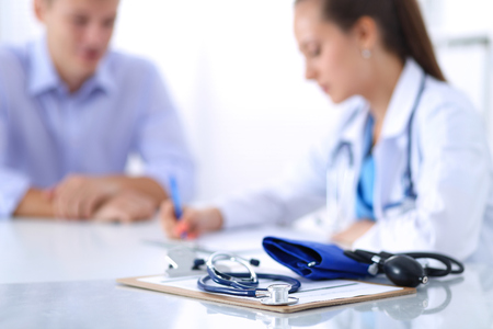 Photo pour Doctor woman sitting with  male patient at the desk . - image libre de droit