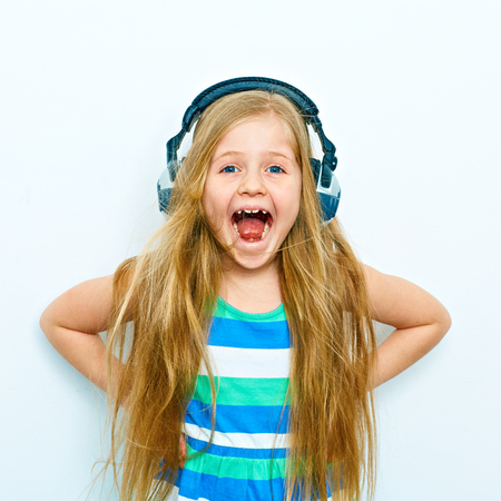 Photo for Screaming little girl with headphones funny portrait isolated on white background. - Royalty Free Image
