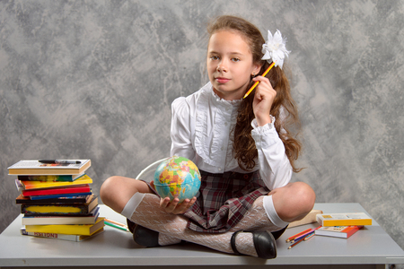 Foto de The fidget schoolgirl in school uniform sits on table and smiles happily on a light gray background. Back to school. The new school year. Child education concept. - Imagen libre de derechos