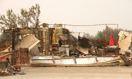 Photo for home burned to the ground, garage door buckled and laying in a heap after the recent wild fire fire storm in Redding, CA. Smoke and ash in the air as the fire continues to burn several miles away. - Royalty Free Image