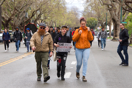 """Photo for Alameda, CA - March 14, 2018: With calls to """"End gun violence, no more silence!"""" hundreds of students from Alameda High School participate in a student walkout to protest gun violence as it starts raining. - Royalty Free Image"""
