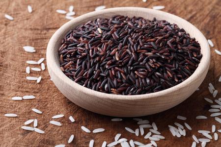 Foto de long grain ricebrown ricein a wooden bowl on wood background - Imagen libre de derechos