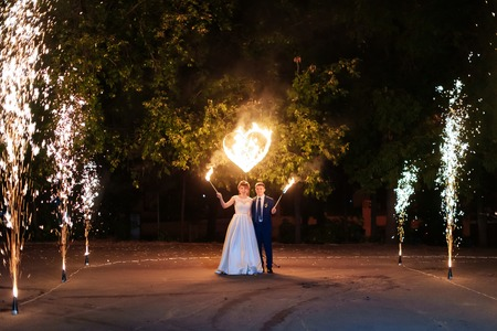 Foto de beautiful young newlywed couple with fire torches in their hands and fireworks - Imagen libre de derechos