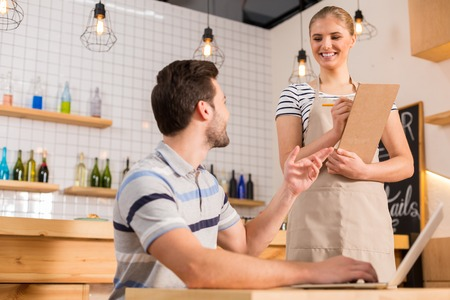Photo for I want food. Joyful nice hungry man looking at the waitress and making an order while being in the cafe - Royalty Free Image