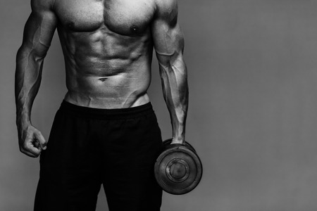 Foto de Close up of muscular bodybuilder guy doing exercises with weights over grey background. Black and white - Imagen libre de derechos