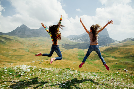 Photo pour two long hair girls happy jump in mountains with exciting view of Montenegro, Durmitor, back view - image libre de droit