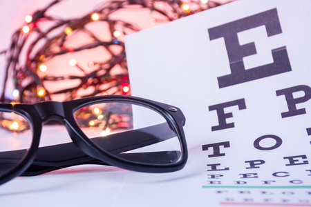 Foto de Christmas and New Year in ophthalmology optometry. Eyeglasses and ophthalmological table for visual acuity test in foreground with blurred lights bulbs Christmas garlands in background - Imagen libre de derechos