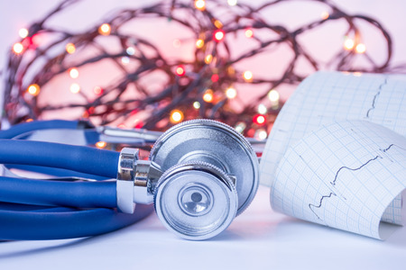 Foto de Christmas and New Year in medicine, general practice or cardiology. Medical stethoscope and ECG tape with pulse trace in foreground with blurred lights bulbs Christmas garlands in background. - Imagen libre de derechos
