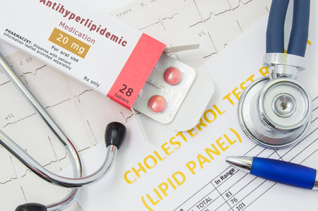 Foto de Antihyperlipidemic drug concept photo. Open packaging with drugs tablets, on which  written Antihyperlipidemic Medication, lies near stethoscope, result analysis on cholesterol (lipid panel) and ECG - Imagen libre de derechos