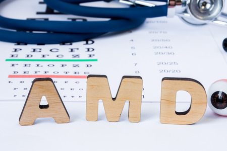 Photo pour AMD Abbreviation or acronym of age-related macular degeneration - eye problem in older persons. Word AMD is on foreground near eye model with stethoscope and visual acuity test on blurry background - image libre de droit