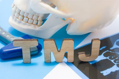 Foto de TMJ medical abbreviation of temporomandibular joint. TMJ letters surrounded by human skull with lower jaw, neurological hammer and radiographs. Concept of anatomy, pathology of temporomandibular joint - Imagen libre de derechos