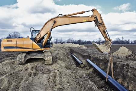 Photo pour Construction site, excavator wearing metal pipe - image libre de droit