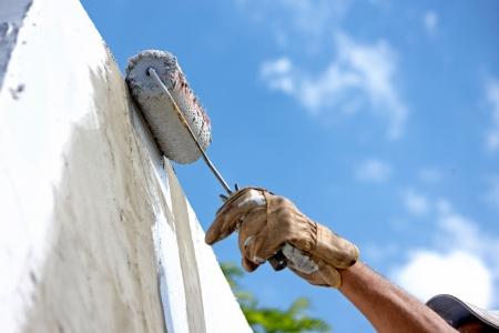 Photo pour builder worker painting facade of high-rise building with roller  - image libre de droit