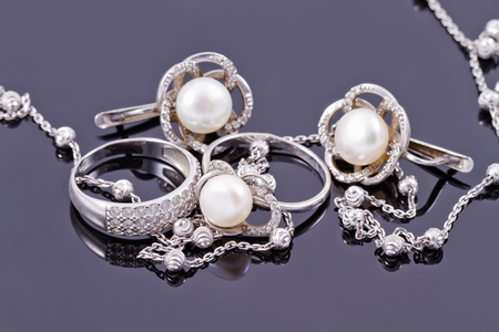 Foto de Fine silver rings are together with unusual silver chain on a white acrylic Board - Imagen libre de derechos